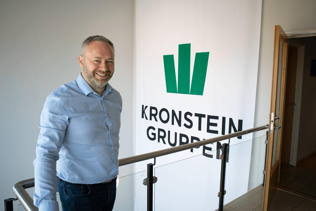 Kristian Eilertsen foran Kronstein Gruppen logoen